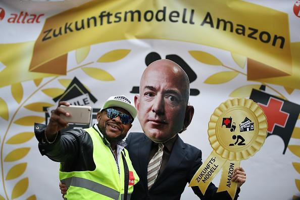 An Amazon warehouse worker shoots a selfie with an activist dressed as Amazon CEO Jeff Bezos during a protest gathering outside the Axel Springer building on April 24, 2018 in Berlin. Several hundred Amazon warehouse workers from Germany, Poland and Italy protested outside the Axel Springer building, where inside Bezos was scheduled to receive an award for innovation. The workers claim Amazon pays too little and offers too few benefits. (Photo by Sean Gallup/Getty Images)