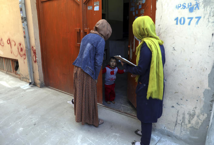 Health workers go door to door during a polio vaccination campaign in the city of Kabul, Afghanistan, Tuesday, March 30, 2021. Three female polio vaccinators were gunned down in separate attacks Tuesday in eastern Afghanistan, provincial officials said. (AP Photo/Rahmat Gul)
