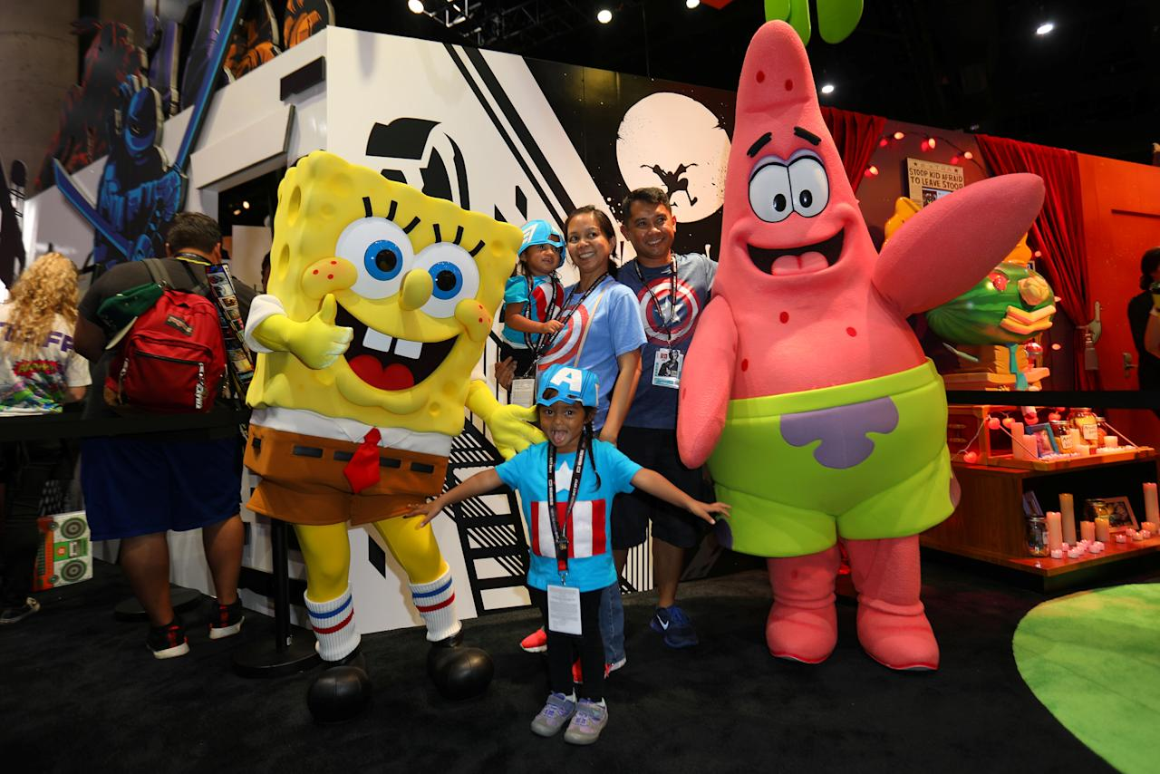 A family poses for a picture with cartoon character Sponge Bob during the opening day of Comic Con International in San Diego, California, U.S., July 20, 2017.     REUTERS/Mike Blake