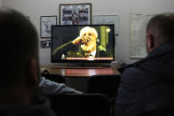 "FILE - In this Wednesday, Nov. 29, 2017 file photo, Bosnian people watch the live TV broadcast from the International Criminal Court for the former Yugoslavia (ICTY) in The Hague as Slobodan Praljak brings a bottle to his lips, in southern Bosnian town of Mostar 140 kms south of Sarajevo. Julian Assange relayed how he ""binge-watched"" the suicide of the former Bosnian Croat general in a United Nations courtroom three years ago, a doctor who visited the WikiLeaks founder on several occasions while he was in the Ecuadorian Embassy in London told an extradition hearing Thursday, Sept, 24, 2020. (AP Photo/Amel Emric, file)"