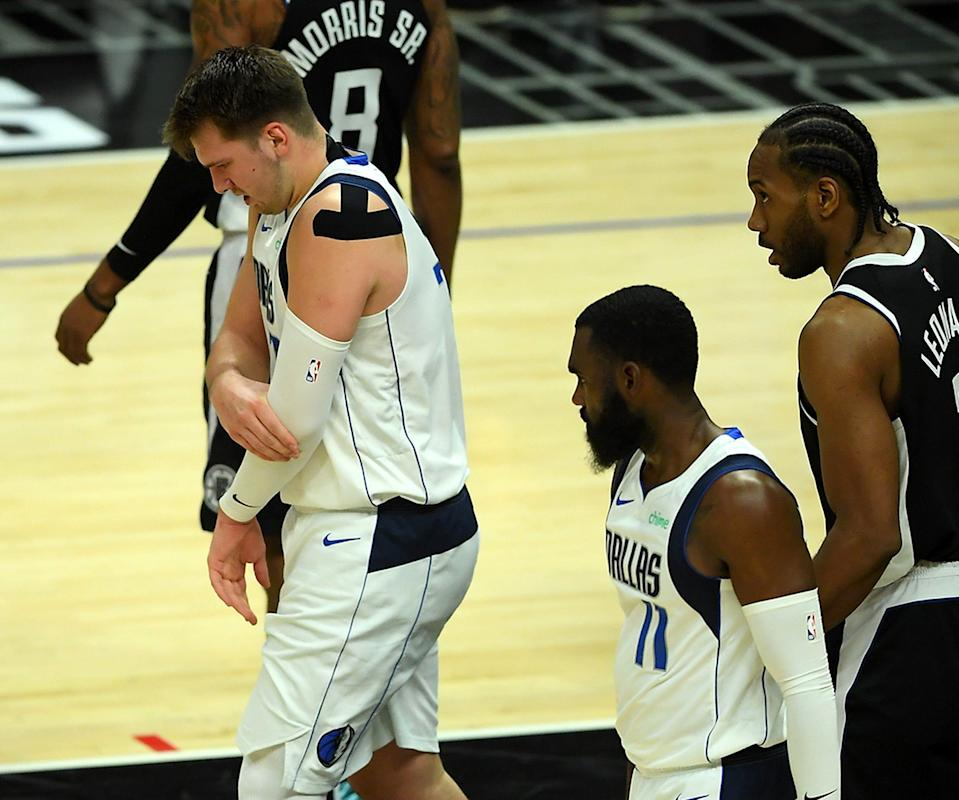 Luka Doncic winces after falling on his left arm during the first half.
