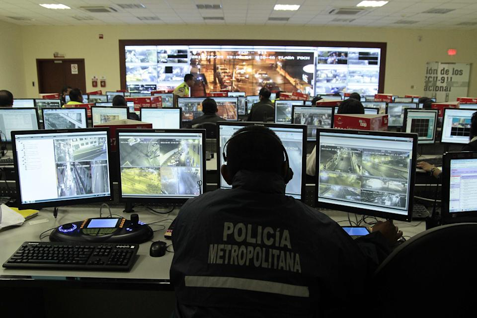 TO GO WITH AFP STORY BY HECTOR VELASCO Picture taken at the Integrated Security Service ECU 911 on November 9, 2013 in Quito. The controversial video surveillance system reached taxis and public buses and quintupled in the last two years  in Ecuador, service director Cesar Navas told AFP. AFP PHOTO/JUAN CEVALLOS        (Photo credit should read JUAN CEVALLOS/AFP/Getty Images)