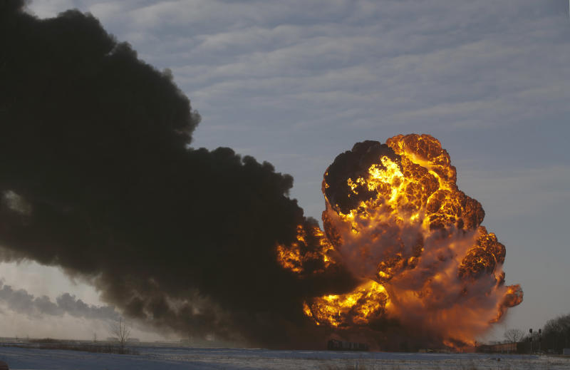 FILE - In this Dec. 30, 2013, file photo, a fireball goes up at the site of an oil train derailment in Casselton, N.D. Trains carrying millions of gallons of explosive liquids, including crude oil, are likely to continue rolling through major cities despite the government's urging to steer the shipments around population centers in the wake of several accidents, according to industry experts. (AP Photo/Bruce Crummy, File)