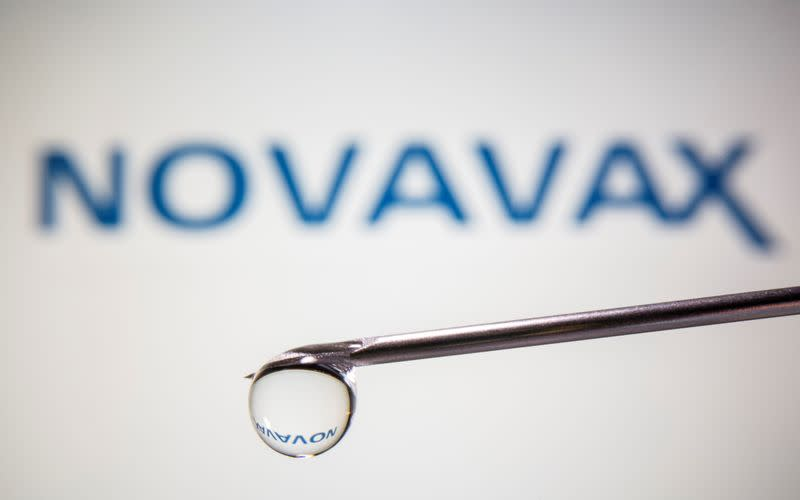 A Novavax logo is reflected in a drop on a syringe needle in this illustration