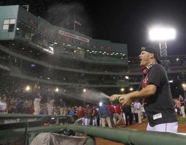 Boston Red Sox relief pitcher Andrew Bailey sprays fans with sparkling wine after the Red Sox clinched the AL East title with a 6-3 win over the Toronto Blue Jays in a baseball game at Fenway Park, Friday, Sept. 20, 2013, in Boston. (AP Photo/Charles Krupa)