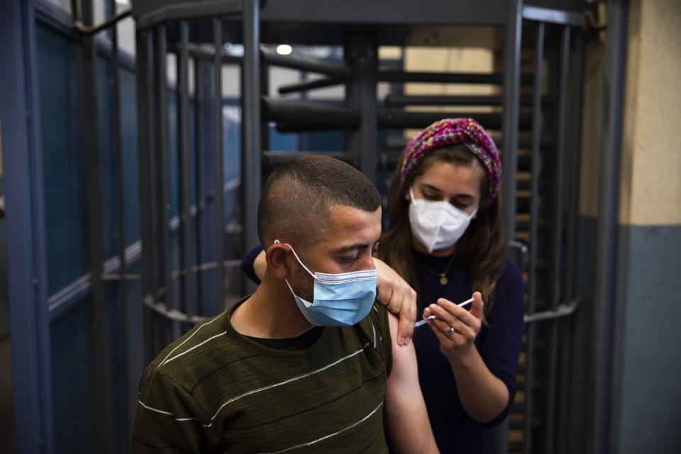A Palestinian laborer who works in Israel receives his first dose of the Moderna COVID-19 vaccine at a coronavirus vaccination center set up at the Meitar checkpoint crossing between Israel and the West Bank, south of the West Bank town of Hebron, Monday, March. 8, 2021. (AP Photo/Oded Balilty)