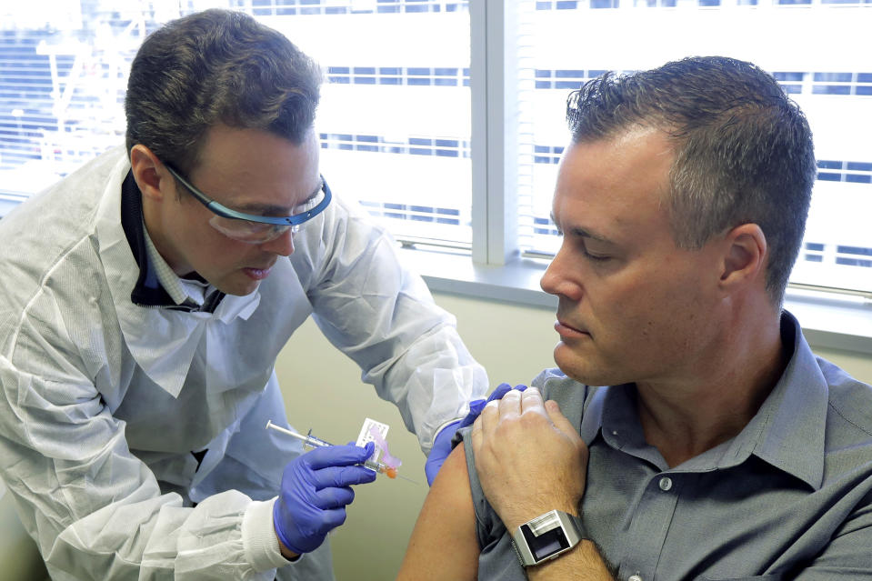 Pharmacist Michael Witte, left, gives Neal Browning a shot in the first-stage study of a potential coronavirus vaccine at the Kaiser Permanente Washington Health Research Institute in Seattle. Source: AP Photo