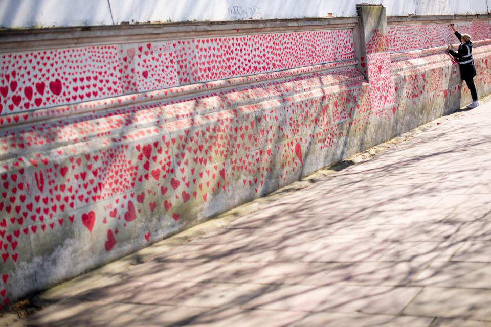 <p>A volunteer adds hearts to the Covid Memorial Wall in central London</p> (PA)