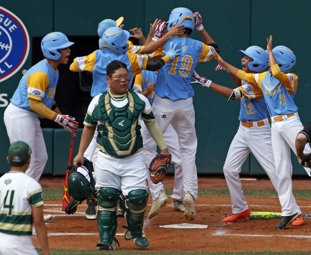 South Korea catcher Gi Jeong Kim, walks to the mound as Honolulu, Hawaii's Mana Lau Kong (19) is greeted by teammates after hitting the first pitch of the baseball game from South Korea's Yeong Hyeon Kim, lower left, for a solo home run in the first inning of the Little League World Series Championship in South Williamsport, Pa., Sunday, Aug. 26, 2018. (AP Photo/Tom E. Puskar).