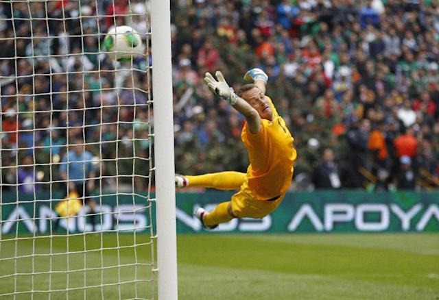 New Zealand goalkeeper Glenn Moss dives for the ball as Mexico scores its 4th goal during a 2014 World Cup playoff first round match in Mexico City, Wednesday, Nov. 13, 2013. (AP Photo/Eduardo Verdugo)