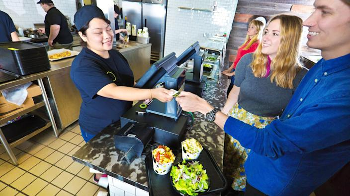 Wait staff and kitchen staff working and serving customers over the counter in a fast food restaurant.
