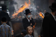 Ultra-Orthodox Jewish men and children, some wearing face mask, burn leavened items in final preparation for the Passover holiday in the ultra-Orthodox Jewish town of Bnei Brak, near Tel Aviv, Israel, Friday, March 26, 2021. Israelis will once again hold large family gatherings this weekend to celebrate Passover, the festive Jewish holiday recalling the biblical flight of the Israelites from Egypt. That's thanks to a highly successful coronavirus vaccination campaign that has inoculated 80% of the country's adult population. (AP Photo/Oded Balilty)