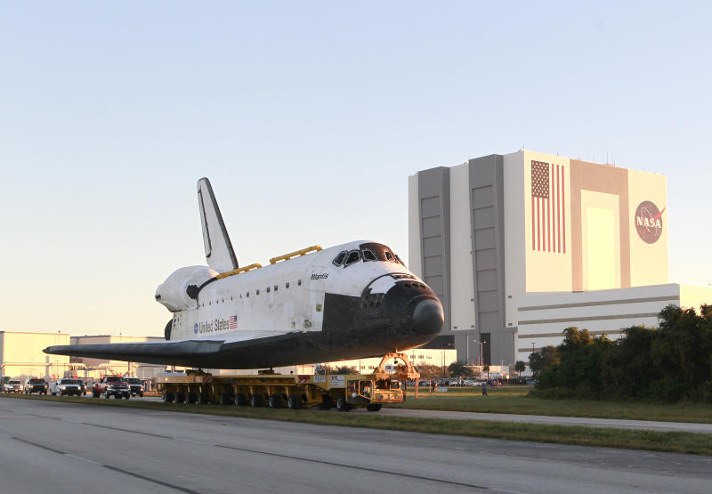 CORRECTS BYLINE TO JOHN RAOUX - Space shuttle Atlantis make its way from the Vehicle Assembly Building to the Visitor Complex at the Kennedy Space Center, early Friday, Nov. 2, 2012, in Cape Canaveral, Fla. Atlantis began its slow journey to retirement Friday, riding atop 76-wheeled platform on the 10-mile trek to the Kennedy Space Center's main tourist stop. (AP Photo/John Raoux)