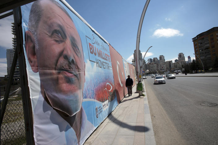 A man walks by huge posters of Turkey's President Recep Tayyip Erdogan, still displayed despite an election ban, near a polling station during the local elections in Ankara, Turkey, Sunday, March 31, 2019. Turkish citizens have begun casting votes in municipal elections for mayors, local assembly representatives and neighborhood or village administrators that are seen as a barometer of Erdogan's popularity amid a sharp economic downturn. (AP Photo/Burhan Ozbilici)