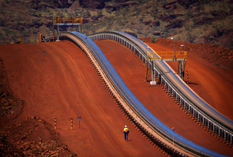 FILE PHOTO: Worker walks near conveyer belts loaded with iron ore at the Fortescue Solomon iron ore mine located in the Valley of the Kings