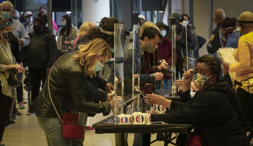 Voters sign in to cast votes at the Madison Square Garden's early voting polling site, Saturday Oct. 24, 2020, in New York. (AP Photo/Bebeto Matthews)
