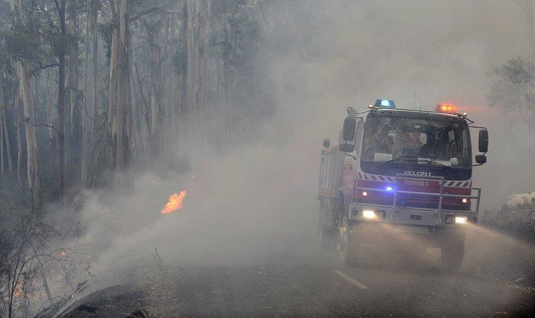 """New South Wales state fire crews drive through the smoke from the Kilmore East-Murrindini North fire on March 3, 2009. The Kilmore East blaze was the largest of the """"Black Saturday"""" February 2009 wildfires in southern Victoria state that left 173 dead and razed more than 2,000 homes, the nation's worst natural disaster of modern times"""