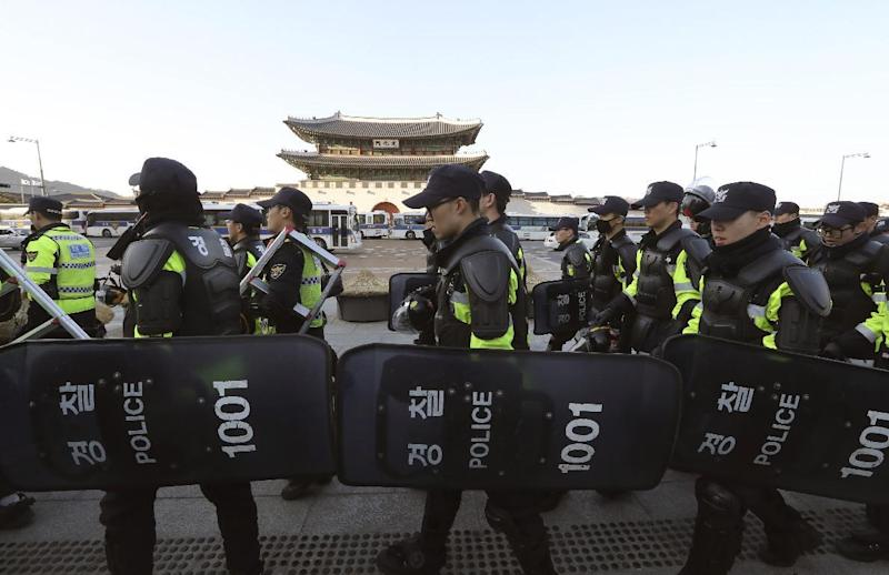Police officers move near the Gwanghwamun, the main gate of the 14th-century Gyeongbok Palace, one of South Korea's well known landmarks, in Seoul, South Korea, Friday, March 10, 2017. In a historic, unanimous ruling Friday, South Korea's Constitutional Court formally removed impeached President Park Geun-hye from office over a corruption scandal that has plunged the country into political turmoil and worsened an already-serious national divide. (AP Photo/Lee Jin-man)
