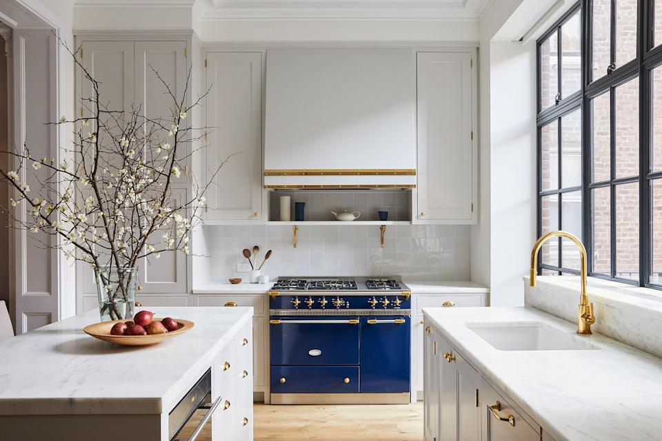 """Marble countertops, brass fixtures, subdued zellige tiles, and a Lacanche range underscore the house's traditional feel in the kitchen, which was designed by Roberts's team under the supervision of project manager Josh Lekwa. """"I love being able to sit at the kitchen counter and look out at the garden,"""" says the homeowner of the back wall of windows."""