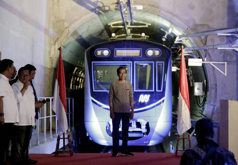 "Indonesian President Joko ""Jokowi"" Widodo, center, stands on a stage with the background of a Jakarta Mass Rapid Transit train during the inauguration ceremony of the subway line in Jakarta, Indonesia, Sunday, March 24, 2019. The 16-kilometer (10-mile) line system running south from Jakarta's downtown is the first phase of a development that if fully realized will plant a cross-shaped network of stations on the teeming city of 30 million people. (AP Photo/Dita Alangkara, Pool)"