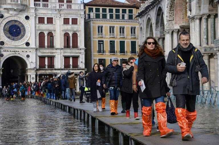 Undeterred by the crisis, tourists have been larking around in the flooded St Mark's Square (AFP Photo/Filippo MONTEFORTE                  )