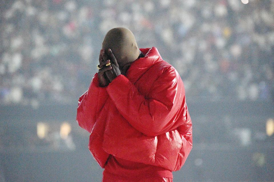 Kanye West is pictured wearing a red puffer coat at his Donda album listening event