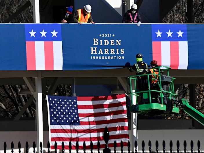 <p>Workers place Biden-Harris inauguration banners on the inaugural parade viewing stand across from the White House in Washington on 14 January 2021.</p> ((Reuters))