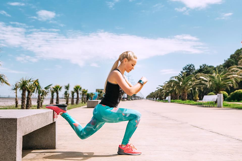 Young woman has an outdoor workout on the sea embankment