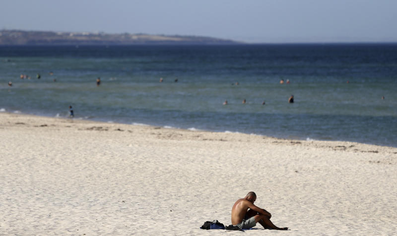 A beachgoer sits in the sun in Adelaide, Australia, in January, where temperatures reached a searing 115.9 degrees Fahrenheit. (ASSOCIATED PRESS)