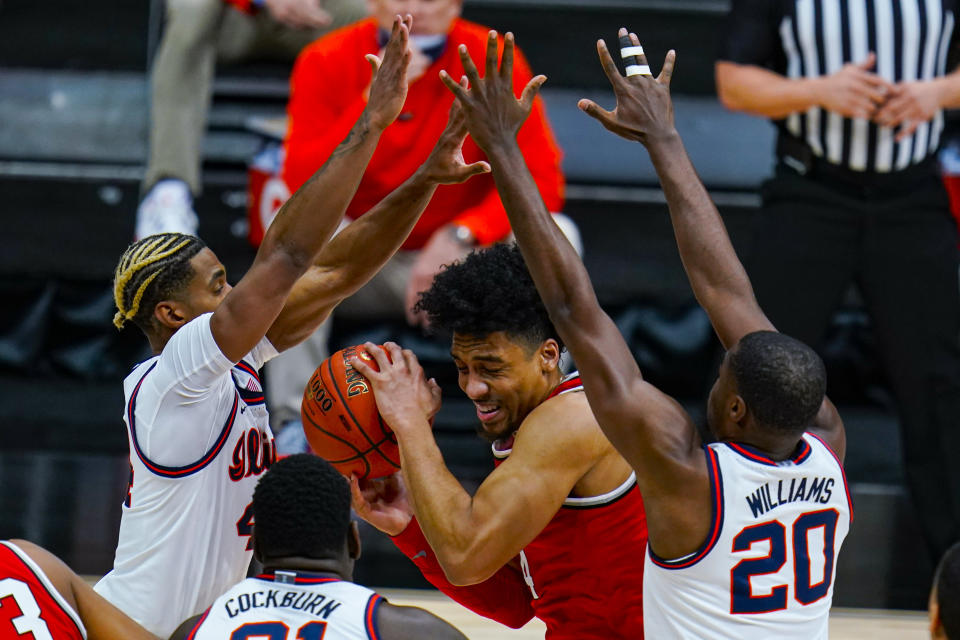 Ohio State forward Justice Sueing, center, is trapped between Illinois forward Zach Griffith, left, and guard Da'Monte Williams, right, in an NCAA college basketball championship game at the Big Ten Conference tournament in Indianapolis, Sunday, March 14, 2021. (AP Photo/Michael Conroy)