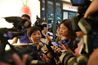 An unidentifed relative (L) of a passenger on board AirAsia flight 8501 is surrounded by the media as she leaves the holding area at Changi international airport terminal in Singapore