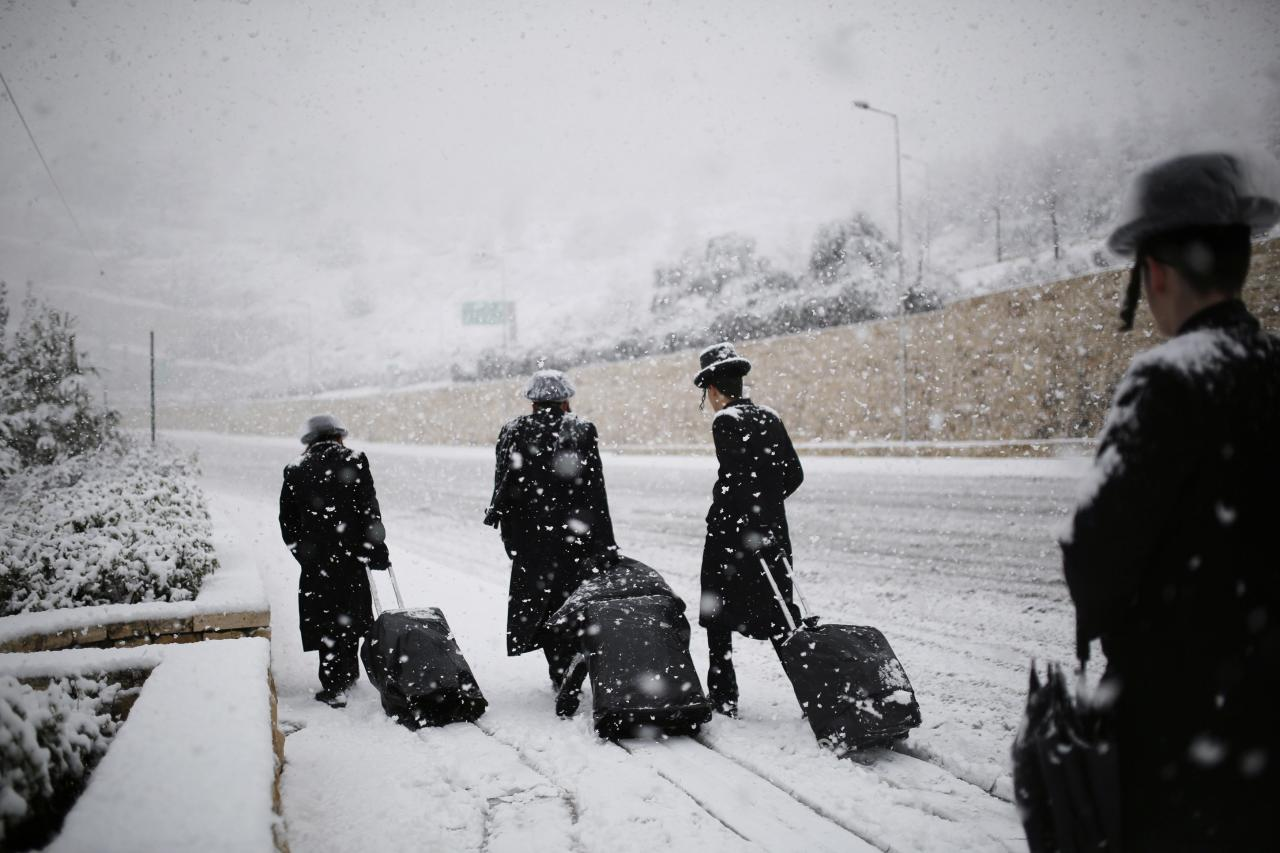 Ultra-Orthodox Jewish men walk on a snow-covered road in winter in Jerusalem