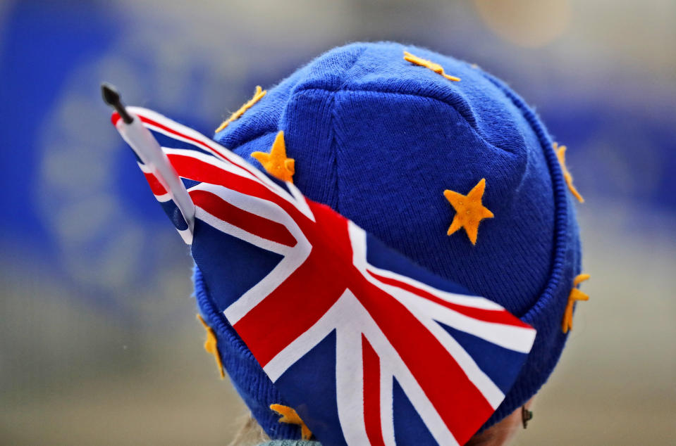 A protestor wears a European hat and a Union Jack flag opposite the Houses of Parliament. (AP Photo/Frank Augstein)