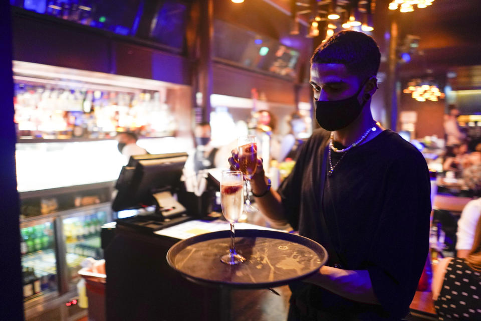 A member of staff wears a face mask as he serves drinks at The Piano Works in Farringdon, in London, on Monday. Photo: AP/Alberto Pezzali