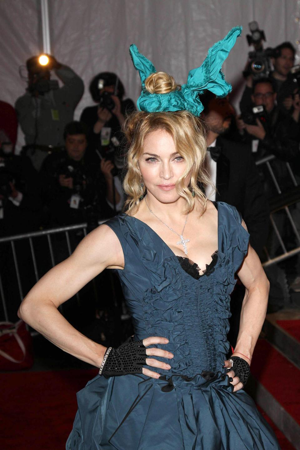 """<p>For the 2009 Met Gala (""""The Model as Muse: Embodying Fashion""""), she wore a <a href=""""https://www.thecut.com/2009/05/thoughts_on_madonnas_ingenious.html"""" rel=""""nofollow noopener"""" target=""""_blank"""" data-ylk=""""slk:headline-generating Marc Jacobs-designed Louis Vuitton ruched minidress"""" class=""""link rapid-noclick-resp"""">headline-generating Marc Jacobs-designed Louis Vuitton ruched minidress</a>, styled with dominatrix boots, turquoise bunny ears, and, yep, a relatively dainty crucifix. <a href=""""https://allaboutmadonna.com/madonna-interviews/madonna-interview-new-york-times-june-29-1986"""" rel=""""nofollow noopener"""" target=""""_blank"""" data-ylk=""""slk:Mused the Material Girl to The New York Times"""" class=""""link rapid-noclick-resp"""">Mused the Material Girl to <em>The New York Times</em></a> of her earliest fashion moments: ''When you go to Catholic school, you have to wear uniforms, and everything is decided for you. Since you have no choice but to wear your uniform, you go out of your way to do things that are different in order to stand out.""""</p><span class=""""copyright"""">Photo: Philip Ramey/Corbis/Getty Images.</span>"""