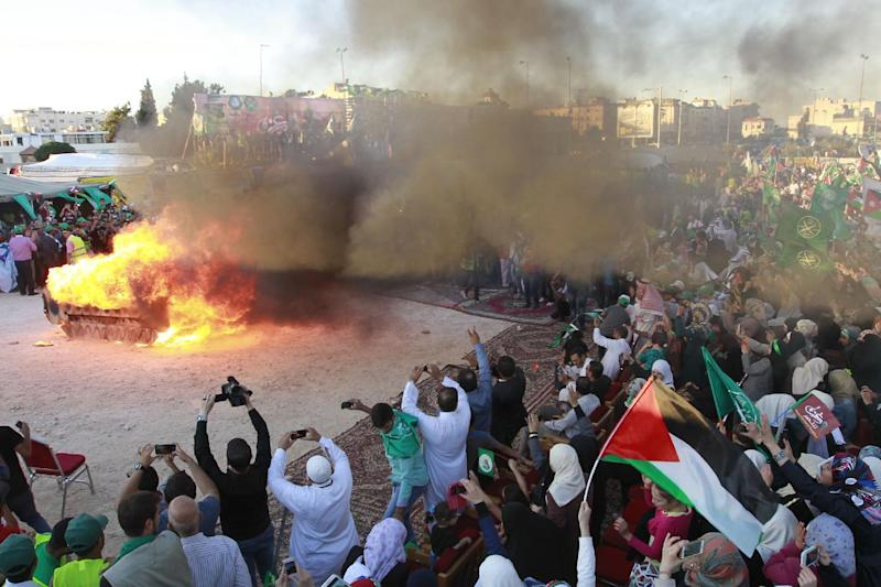 "Jordanian supporters of the Muslim Brotherhood set fire to a mock Israeli tank during a protest to celebrate the ""Gaza victory"" in the war against Israel, in the capital Amman on August 8, 2014"
