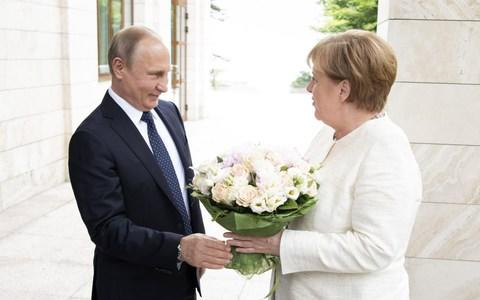 German Chancellor Angela Merkel is handed over a bouquet of flowers as she meets Russian President Vladimir Putin - Credit: Getty Images Europe