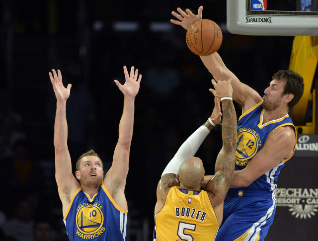 Oct 9, 2014; Los Angeles, CA, USA; Golden State Warriors center Andrew Bogut (12) blocks the shot of Los Angeles Lakers forward Carlos Boozer (5) during the first half at Staples Center. (Richard Mackson-USA TODAY Sports)