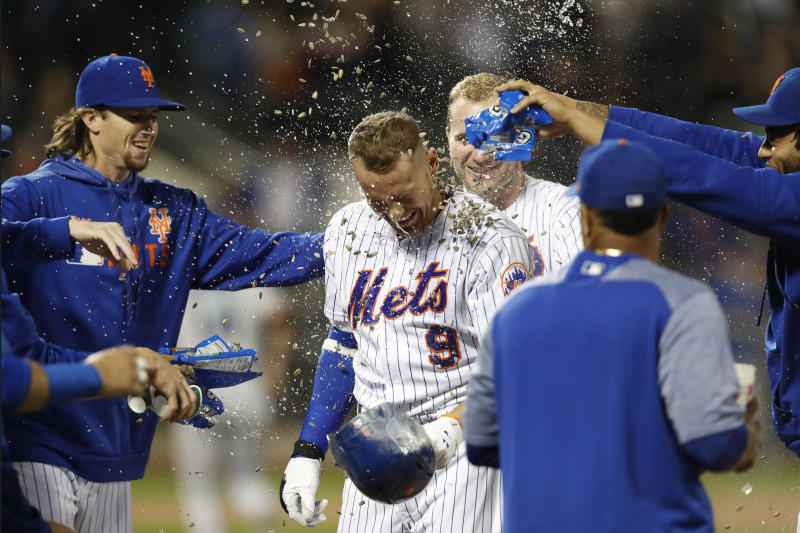 New York Mets' Brandon Nimmo (9) is showered with sunflower seeds after he drew a bases-loaded walk to drive in the winning run against the Miami Marlins in the 11th inning of a baseball game Tuesday, Sept. 24, 2019, in New York. The Mets won 5-4. (AP Photo/Kathy Willens)