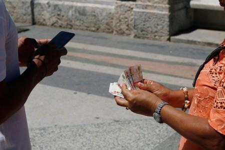 Jason Sanchez makes a transaction with cryptocurrency using the startup Fusyona near the seafront Malecon in Havana