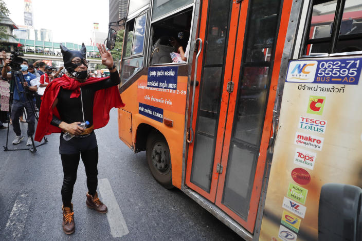 A Pro-democracy protester dressed in costume flash the three-finger protest salute at a major intersection in Bangkok, Thailand, Wednesday, Nov. 18, 2020. Police in Thailand's capital braced for possible trouble Wednesday, a day after a protest outside Parliament by pro-democracy demonstrators was marred by violence that left dozens of people injured. (AP Photo/Sakchai Lalit)