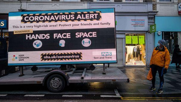 PHOTO: A man looks at a huge coronavirus alert sign warning members of the public to be vigilant in Putney, South West London, on Dec. 23, 2020. (Alex Lentati/London News Pictures via ZUMA Wire via Newscom)