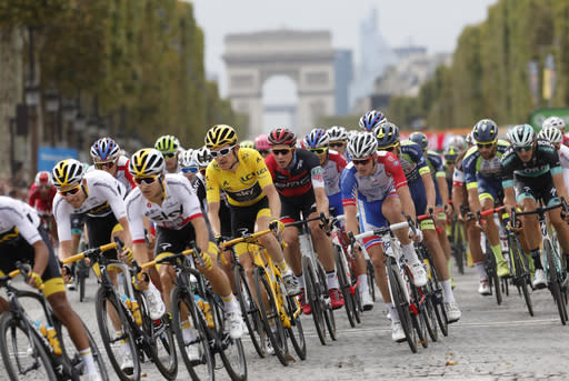Tour de France winner Britain's Geraint Thomas, wearing the overall leader's yellow jersey, follows teammate Poland's Michal Kwiatkowski, second left, and Britain's Luke Rowe, left, as they ride down Chams Elysees avenue as the Arc de Triomphe is seen in the background during the twenty-first stage of the Tour de France cycling race over 116 kilometers (72.1 miles) with start in Houilles and finish on Champs-Elysees avenue in Paris, France, Sunday July 29, 2018. (AP Photo/Laurent Cipriani )