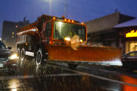 A sanitation truck fitted with a plow treats Lefferts Boulevard in the Queens borough of New York as snow starts to fall, Wednesday, Dec. 16, 2020. (AP Photo/Frank Franklin II)
