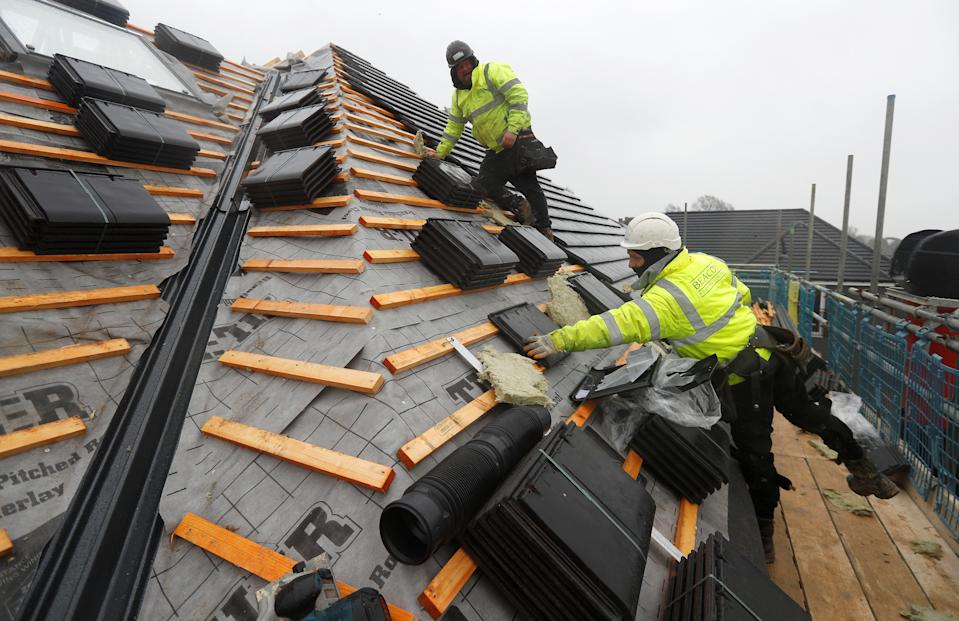 Builders work on the roof of a building at a Barratt housing development near Haywards Heath, Britain. Photo: Peter Nicholls/Reuters