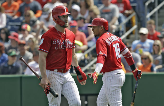 Philadelphia Phillies' Bryce Harper, left, celebrates with on-deck batter Cesar Hernandez after scoring on a throwing error by Detroit Tigers shortstop Willi Castro on a ground ball by Phillies' Odubel Herrera during the seventh inning of a spring training baseball game Wednesday, March 20, 2019, in Clearwater, Fla. (AP Photo/Chris O'Meara)
