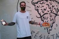 """Funky Pizza restaurant owner Carlos Manich poses as he holds his mobile phone with the """"Funky Pay"""" app in one hand and a pizza in the other, at Funky Pizza restaurant, where the app replaces waiters, in Palafrugell"""
