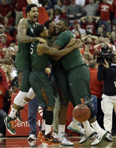 Miami's Reggie Johnson, right, is congratulated by teammates Julian Gamble, left, Rion Brown and Kenny Kadji after shooting the game-winning shot to defeat North Carolina State as time expired in the second half of an NCAA college basketball game in Raleigh, N.C., Saturday, Feb. 2, 2013. Miami won 79-78. (AP Photo/Gerry Broome)