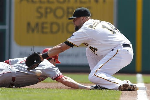 The ball gets past Pittsburgh Pirates first baseman Casey McGehee (14) on a pickoff throw by Charlie Morton as Cincinnati Reds' Drew Stubbs dives back in the first inning of a baseball game Sunday, May 6, 2012, in Pittsburgh. Stubbs got up and went to third on the play. (AP Photo/Keith Srakocic)