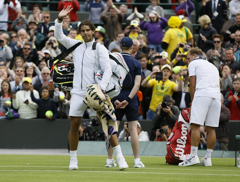 Rafael Nadal of Spain, left, waves to spectators after losing to Steve Darcis of Belgium, right, in their Men's first round singles match at the All England Lawn Tennis Championships in Wimbledon, London, Monday, June 24, 2013. (AP Photo/Kirsty Wigglesworth)